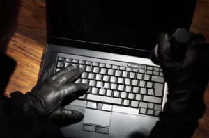 Burglar holding a torch stealing data from a laptop concept for computer security, corporate or identity theft